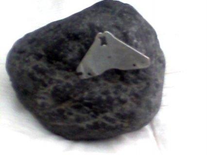 حجر او ليزك قديم لونه اسود ويتمسك به مغناطيس